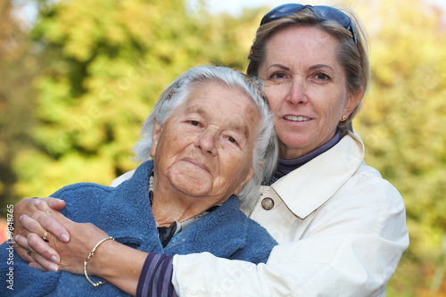 Middleaged woman cuddles her elderly mother