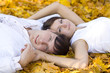 happy couple laying on yellow leaves