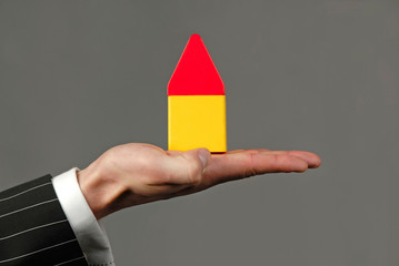 hand with symbolical model of  house on  grey background