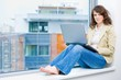 Young businesswoman sitting at office window,