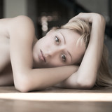 Portrait of a young girl lying on the floor feeling sad. poster