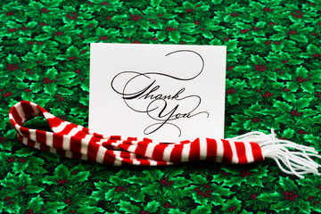 Thank you card and striped scarf on leaf and holly berry