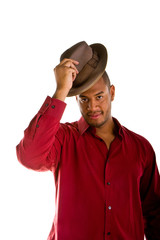 A black man dresses casually tipping a brown fedora