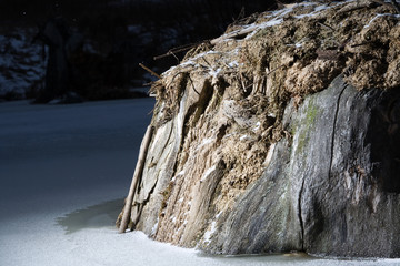 snag stump at the middle of frozen pond in winter night