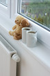 Two teddy bears sitting on radiator in home.