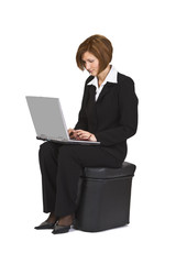 Businesswoman sitting on a pouffe and working on a laptop.