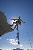Climber beginning her descent from the summit of a rock spire. poster