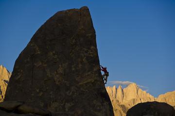 Climber asscending the sheer edge of a pinnacle.