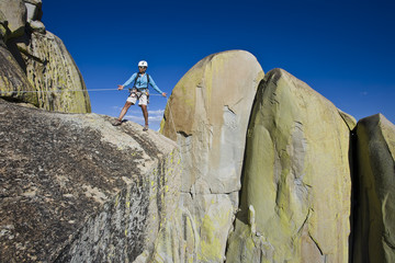 Climber beginning her descent from the summit of a rock spire.