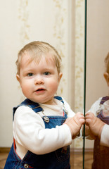 Small smiling baby playing with mirror at home