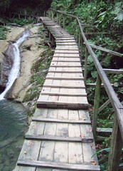 a wooden bridge over waterfall