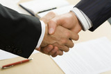 Photo of business handshake over workplace poster