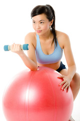 A young attractive Asian woman working out with dumbbells