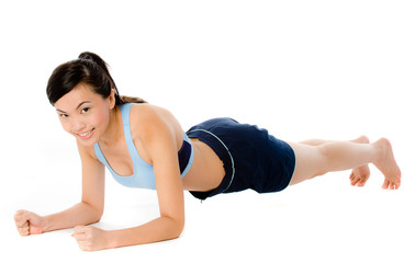 A young attractive Asian woman doing a plank pose