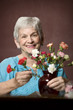 Senior woman at home with colorful flowers
