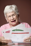 Upset senior woman with many bills and notices poster
