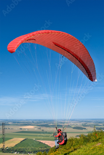 Paraglider with red parachute taking off from the hill
