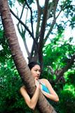 Asian girl outside hugging long thin tree poster