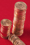 Euro cooper coins in piles on red.