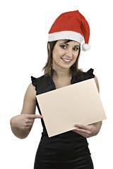 Chica sonriente con gorro de Santa Claus y cartel en blanco