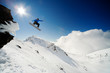 Snowboarder jumping through air from rock drop