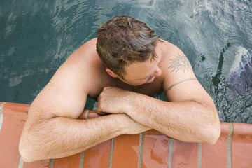 Man relaxing in a swimming pool.