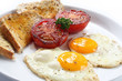 Breakfast of fried eggs and tomatoes, with wholewheat toast.
