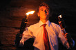 Young businessman lighting with torch in a cave