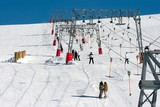 Skiers using a ski lift at a winter resort poster