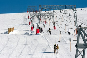 Skiers using a ski lift at a winter resort