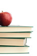 A red apple on top of many books on a white background