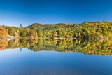 Lush fall foliage reflecting in an amazingly smooth lake poster