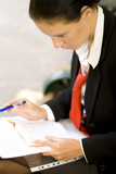businesswoman is writing notes and planning her schedule poster
