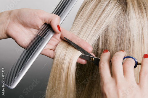 hairdresser cutting blonde hair. closeup over grey background