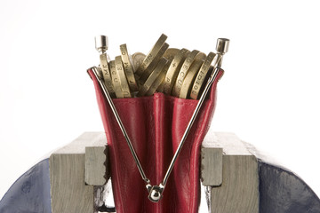Ladies purse filled with pound coins being squeezed in vice