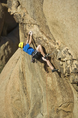 Climber scaling an overhanging rock face.