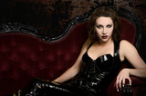 Beautiful young woman in latex catsuit on classic red couch poster