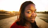 Pretty African American woman in an urban setting at sundown poster
