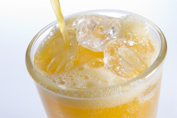 Pouring Orangeade Into A Glass Of Ice