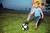 Boy playing football with his dad outdoors at twilight poster