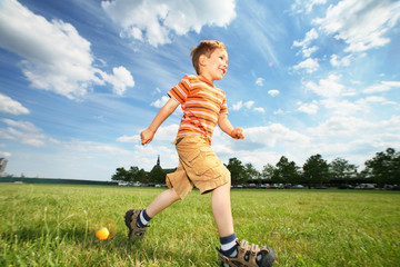 Boy running outdoors under beautiful blue sky