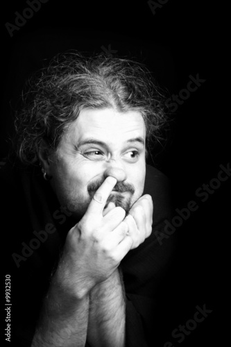 Black and white portrait of the young man picking his nose