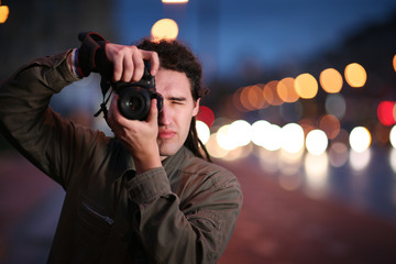 Photographer taking photo with DSLR camera at night