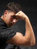 strong man showing his bicep against dark background poster