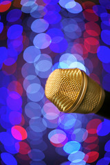 A microphone alone full of out of focus clor lights