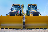 Two new bulldozers on a showcase . poster