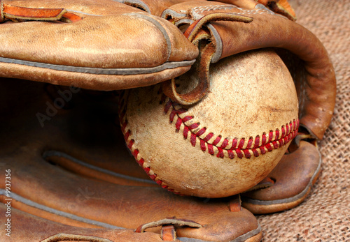 Worn and used baseball in the pocket of a baseball mitt.
