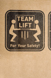 A safety label on a cardboard box instructing to