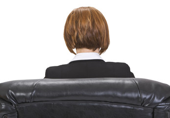 Rear image of a businesswoman sitting in an armchair.