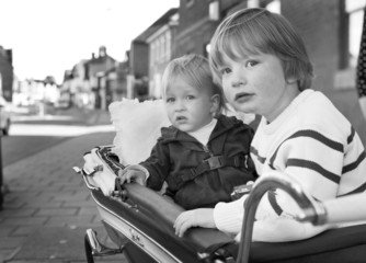 two boys sit in his 1950's Silver Cross perambulater